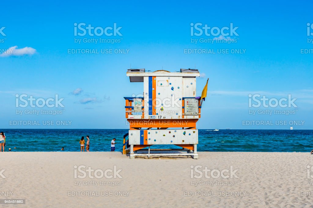 People enjoy the beach next to a lifeguard tower stock photo