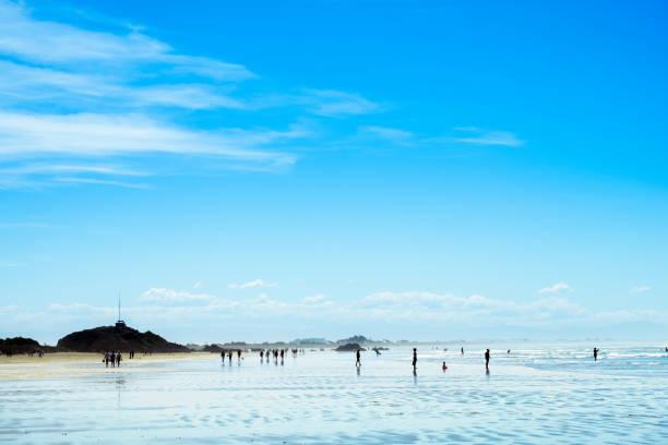 Menschen genießen ihre Aktivitäten am wunderschönen Strand an einem sonnigen blauen Himmel Tag. – Foto