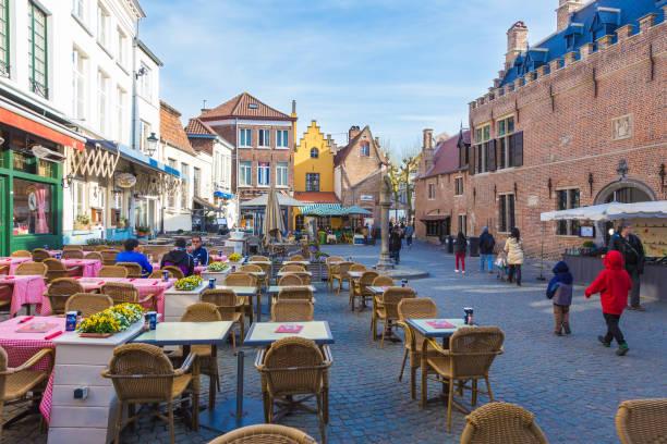 as pessoas gostam de seu dia ao longo de uma rua e lojas em bruges, cidade da bélgica património mundial, num dia de primavera, de 11 de abril de 2017 - fine dining - fotografias e filmes do acervo