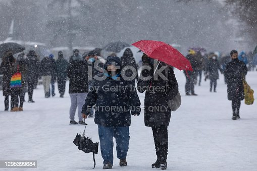 Madrid, Spain - January 08, 2021: People enjoying a walk through the Buen Retiro park in Madrid, in the middle of a snowy day, due to a wave of polar cold.