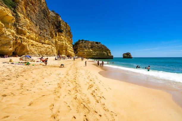 People enjoying a sunny day at Marinha Beach (Praia da Marinha), a beautiful sandy beach in Algarve, Lagoa, Portugal stock photo