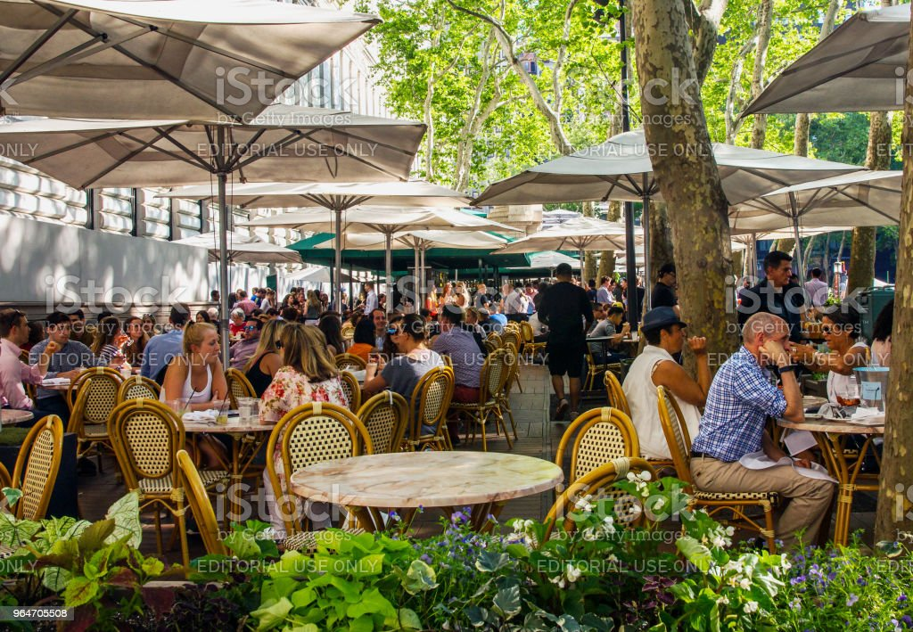 People Enjoying Al Fresco Dinning at Bryant Park Cafe in New York royalty-free stock photo