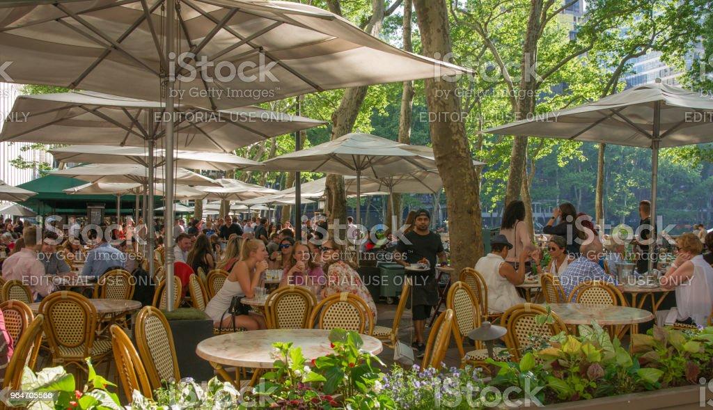 People Enjoying Al Fresco Dinning at Bryant Park Cafe in New York royalty-free stock photo