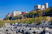 People are walking, jogging and resting on benches in Brooklyn Bridge Park on a bright Autumn Afternoon.