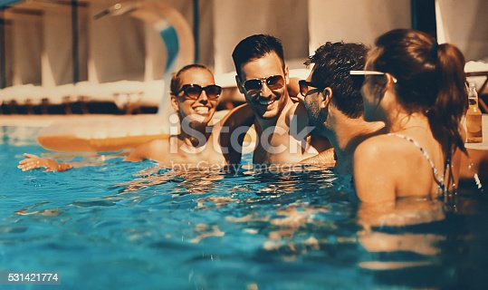 Two couples having beers while relaxing by the poolside of the hotel they stayed in. Their vacation has just started. Mid 20's men and women. Each person is wearing sunglasses.