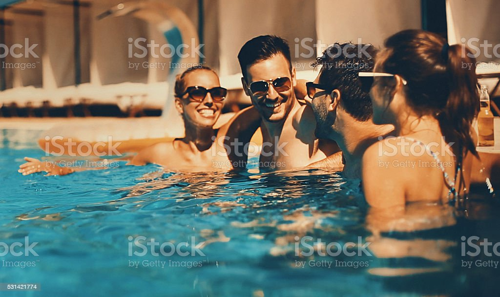 People enjoying drinks by the swimming pool. stock photo