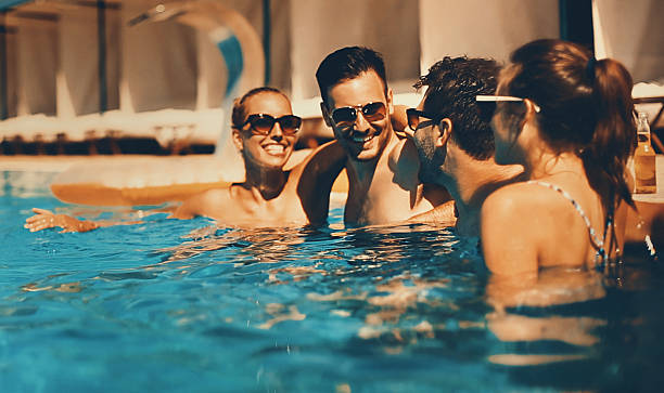 People enjoying drinks by the swimming pool. Two couples having beers while relaxing by the poolside of the hotel they stayed in. Their vacation has just started. Mid 20's men and women. Each person is wearing sunglasses. poolside stock pictures, royalty-free photos & images