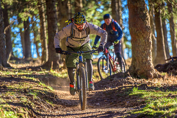 People enjoying mountain biking People enjoying mountain biking in forest with trees in background. mountain biking stock pictures, royalty-free photos & images