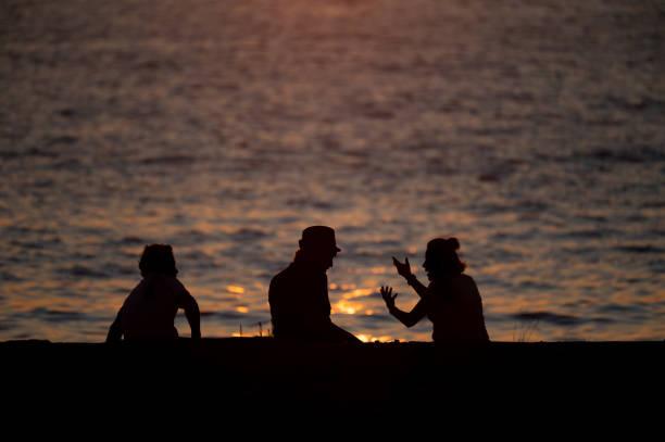 People enjoying seascapes on the shore during sunset. stock photo