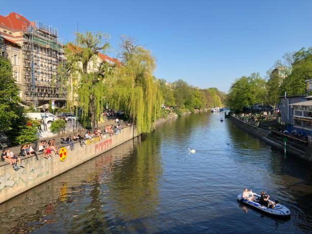 menschen genießen sonniges wetter auf der straße, sitzen am flussufer in berlin, kreuzberg im frühling - kreuzberg stock-fotos und bilder
