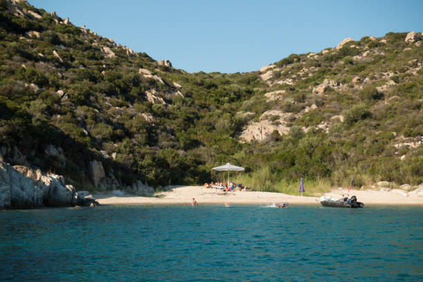 People enjoying the summer in a secluded beach in Sithonia, Greece stock photo