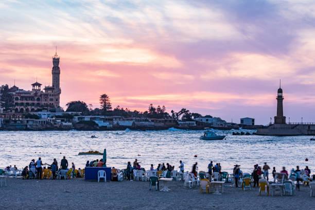 People enjoying the sunset along the harbor in Alexandria stock photo
