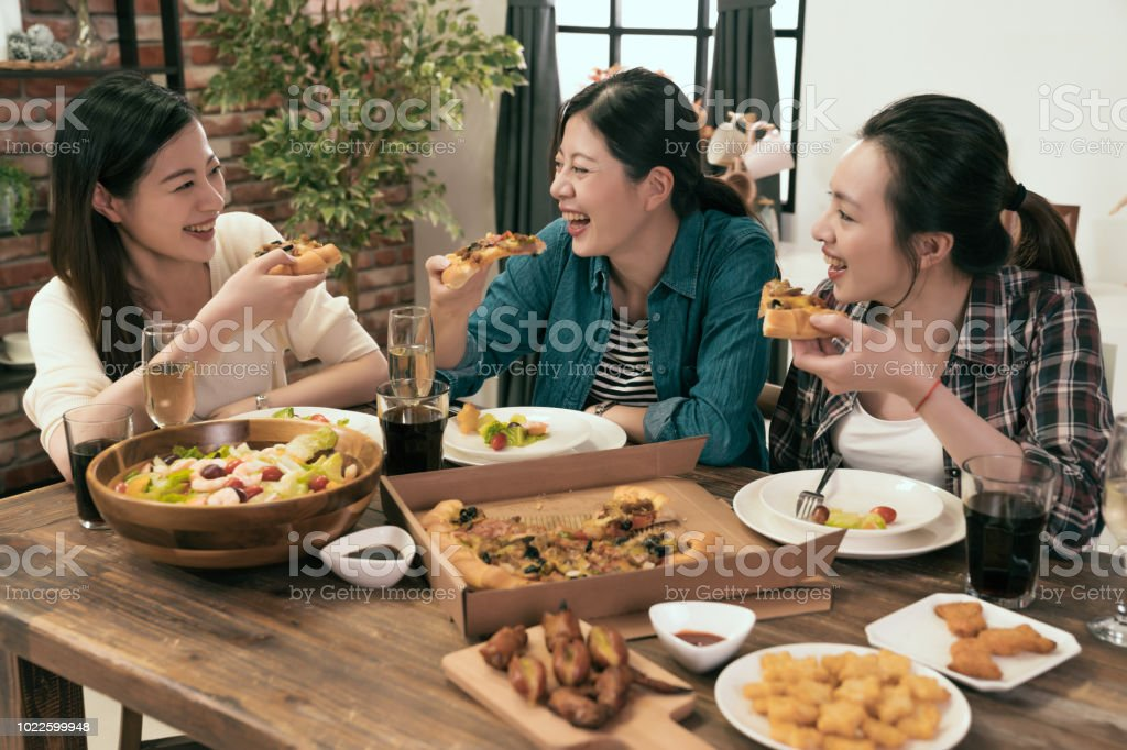 people enjoys pizza together at home stock photo