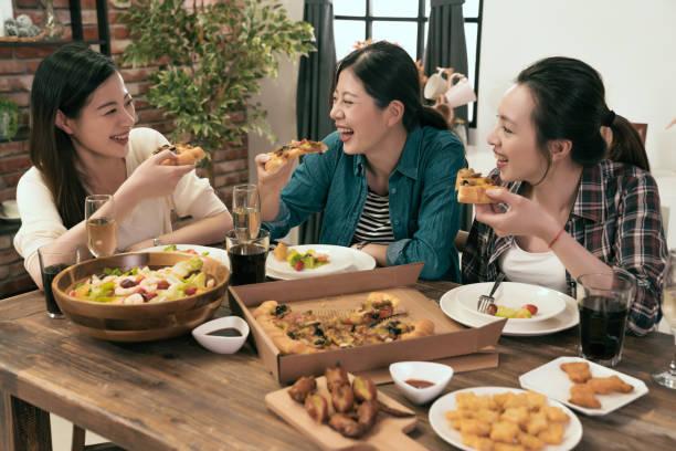 自宅の人々 はピザを一緒に楽しんで - 姉妹 ストックフォトと画像