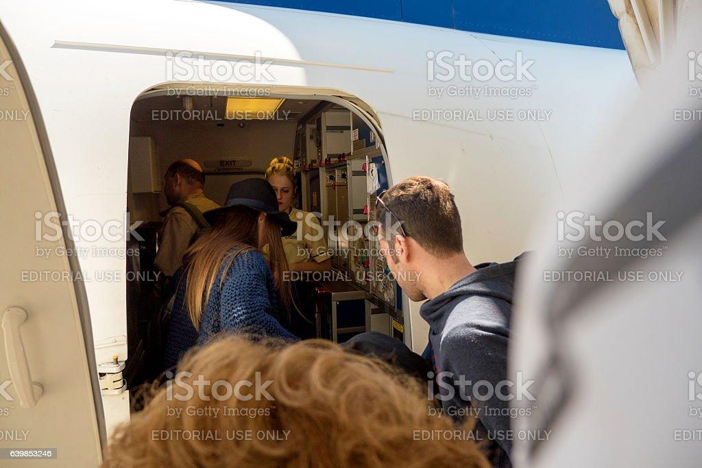 People entering airplane through door airport stock photo