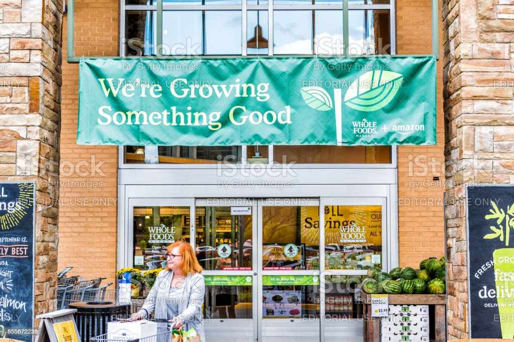 People entering exiting Whole Foods Market building in city in Virginia with Amazon or Amazon.com partnership banner stock photo