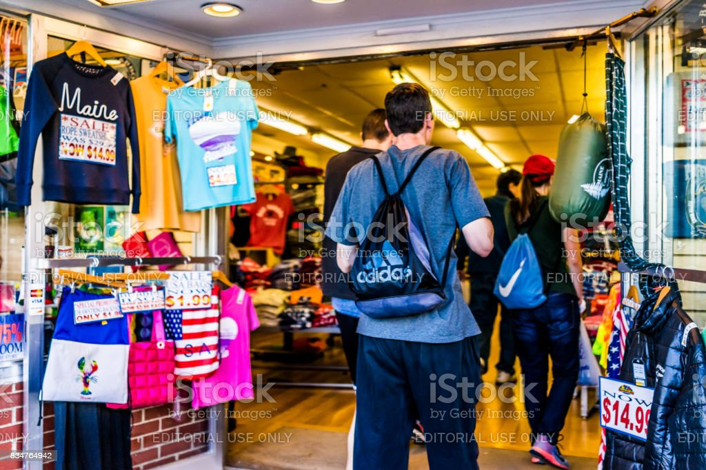 People entering souvenir gift store in downtown village in summer by stores stock photo