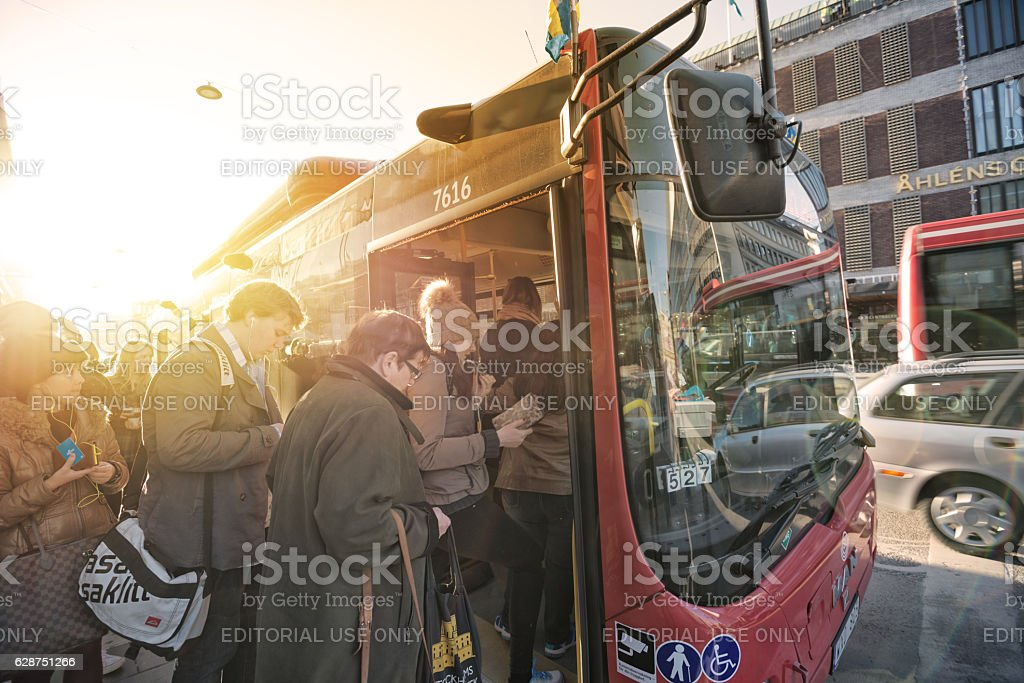 People enters bus at busstop stock photo