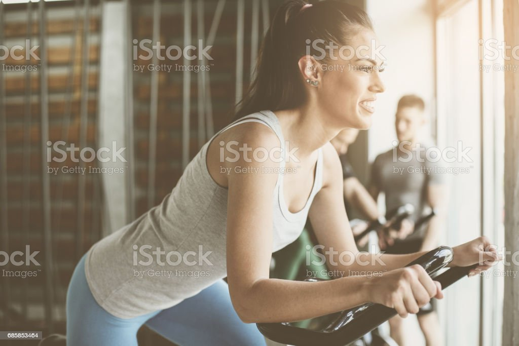 People exercise on stationary bikes in fitness class. People workout in gym. Exercise on elliptical machine. Man personal trainer. stock photo