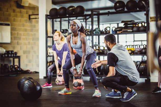 personas ejercitando en un gimnasio con bolas de medicina - entrenador personal fotografías e imágenes de stock