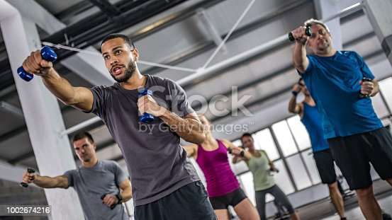 Men and women exercising with dumbbells in gym.