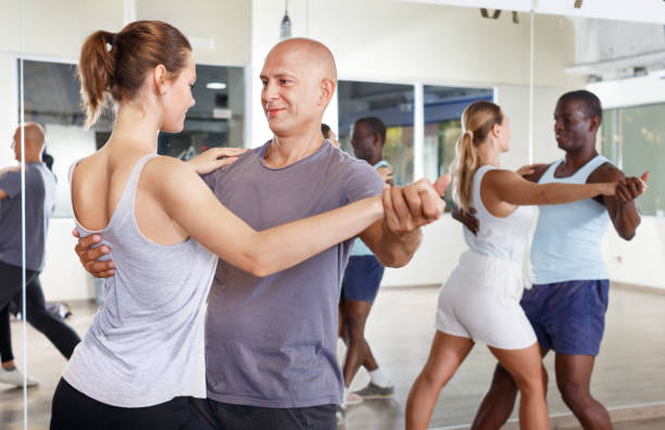 People exercising waltz movements in pairs stock photo