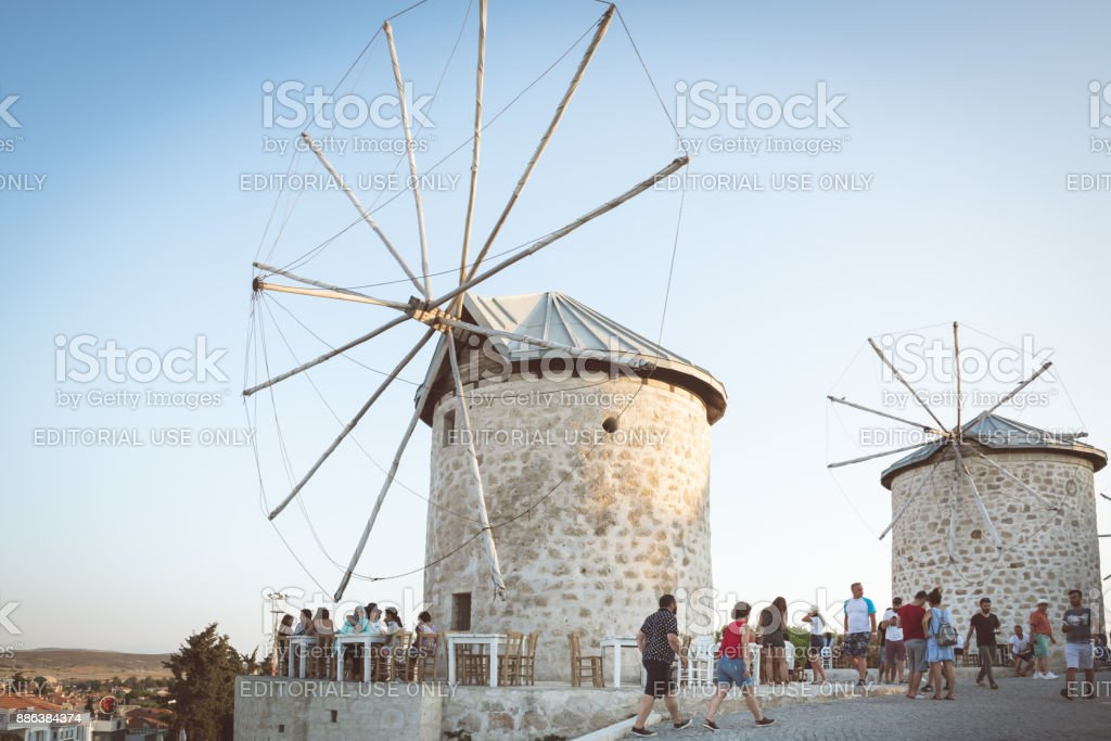 People exploring ancient old stone windmills in Alacati stock photo