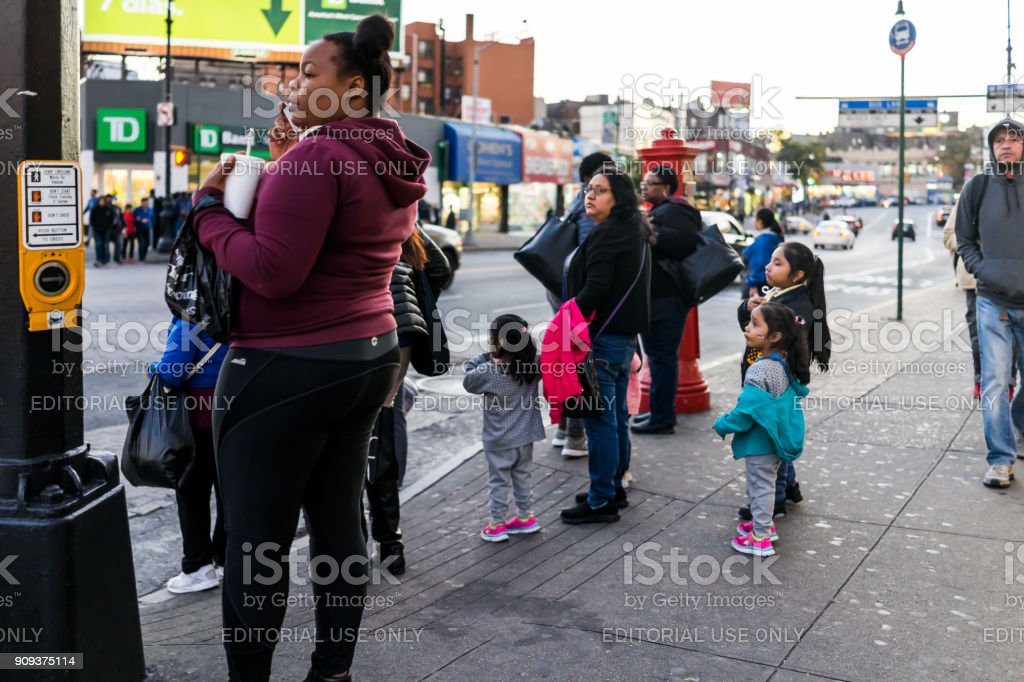 People family waiting to cross street in Fordham Heights center, New York City, NYC in evening stock photo