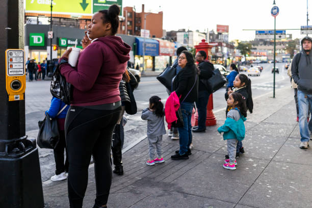 people family waiting to cross street in fordham heights center, new york city, nyc in evening - poverty stock pictures, royalty-free photos & images