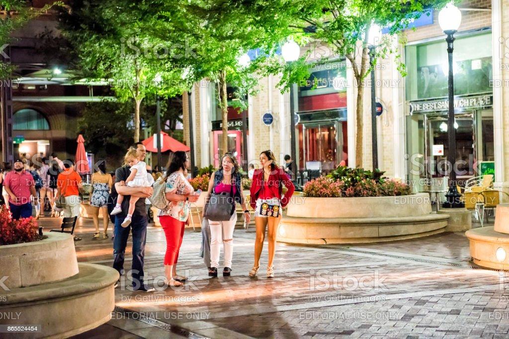 People Family Walking On Sidewalk By Restaurants In