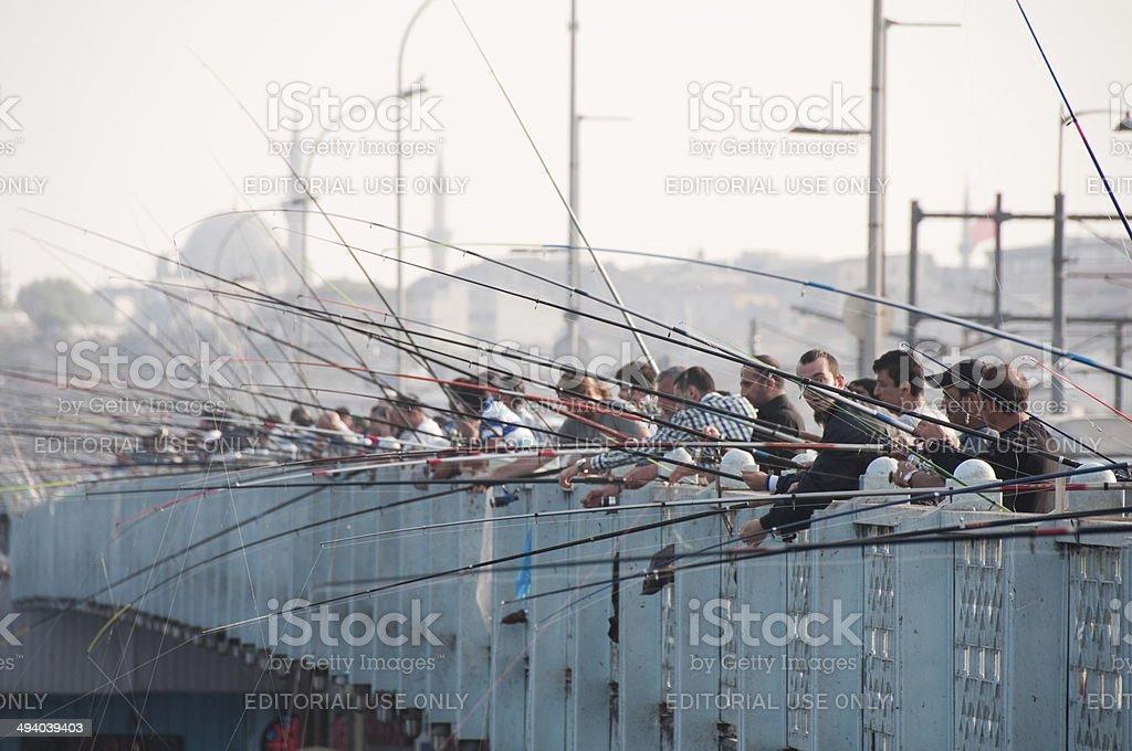 People fish from the Galata bridge, Istanbul stock photo