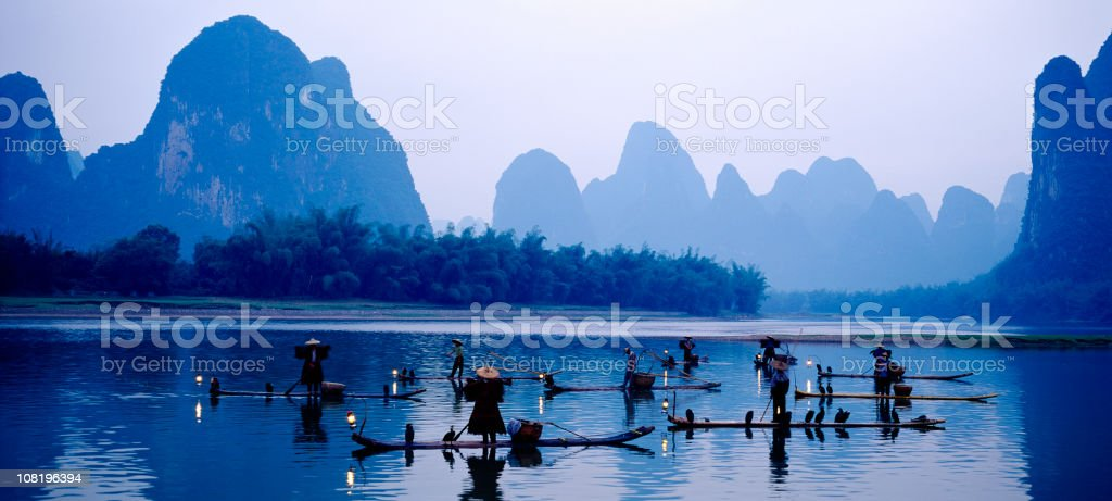 People fishing in the lake near the mountains stock photo