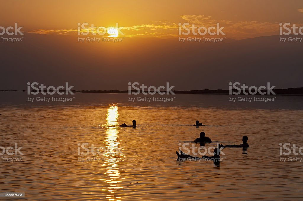 People floating at the Dead sea at dawn, Israel royalty-free stock photo