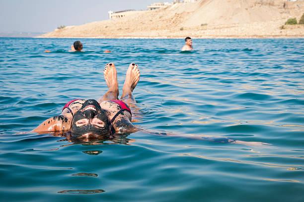 people floating in the dead sea in jordan - morze martwe zdjęcia i obrazy z banku zdjęć