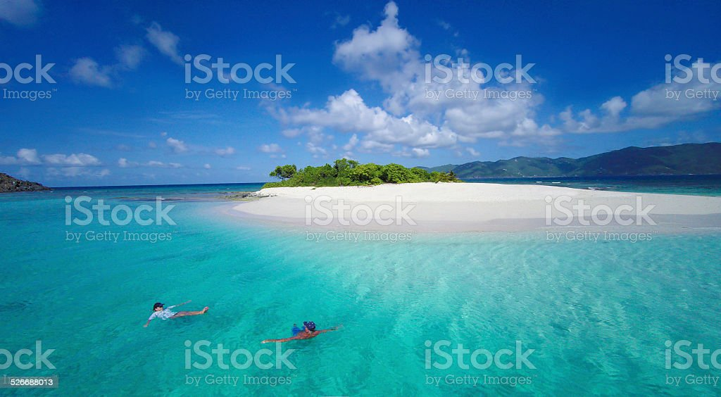 people floating on water by Sandy Spit, British Virgin Islands stock photo