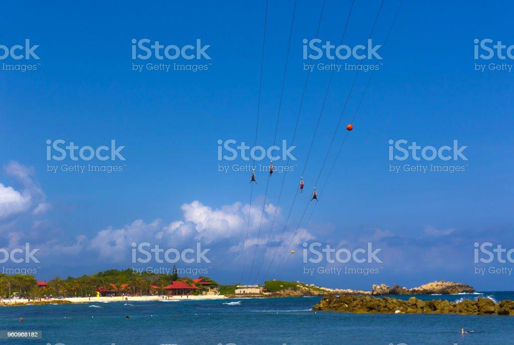 People flying at high zipline on caribbean stock photo