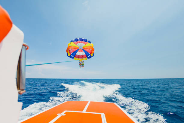 People flying on a colorful parachute towed by a motor boat stock photo