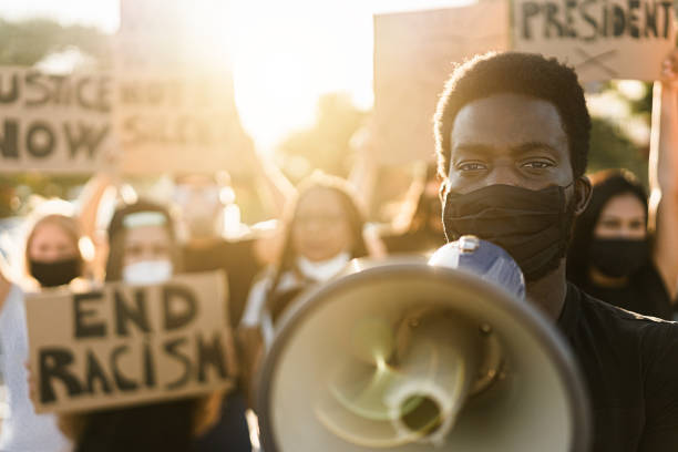 People from different culture and races protest on the street for equal rights People from different culture and races protest on the street for equal rights. Focus on black man eyes protest stock pictures, royalty-free photos & images