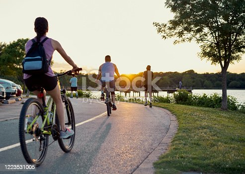 Bikers and runners doing sports over a trail in White Rock lake, Texas during sunset time. De-scale period.