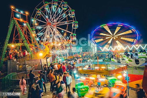 Solan, Himachal Pradesh, India - September 22, 2019: A high and wide-angle view shows a large number of people gather in Himachal Utsav fair to take rides on various swings and ferries wheel. Himachal Utsav fair takes place every year in September in Thodo ground, Solan. It is organized and started in 2003 by an NGO called Dynamic India Yuva Mandal to promote art, culture, trade, food, rural sports of Himachal Pradesh and other states of India in Solan. The big crowd of people participates in the fair with great interest.