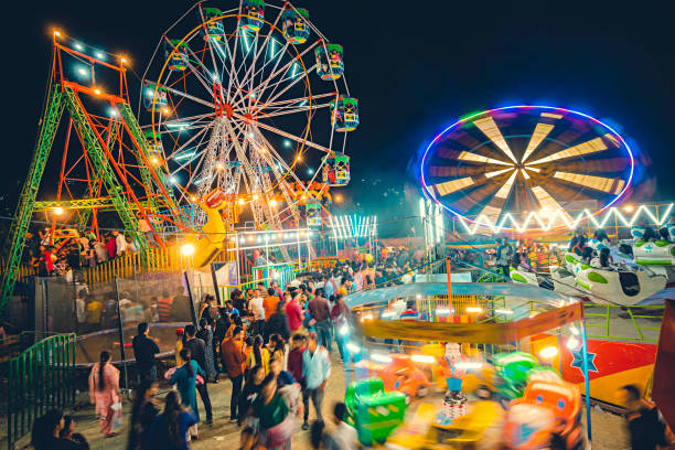 People gather to take a ride on a different swings and ferries wheel in Himachal Utsav fair. stock photo