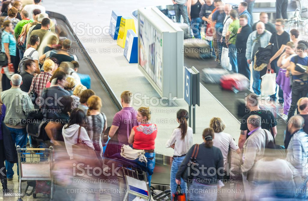 people getting luggage from conveyor belt at airport after flight stock photo