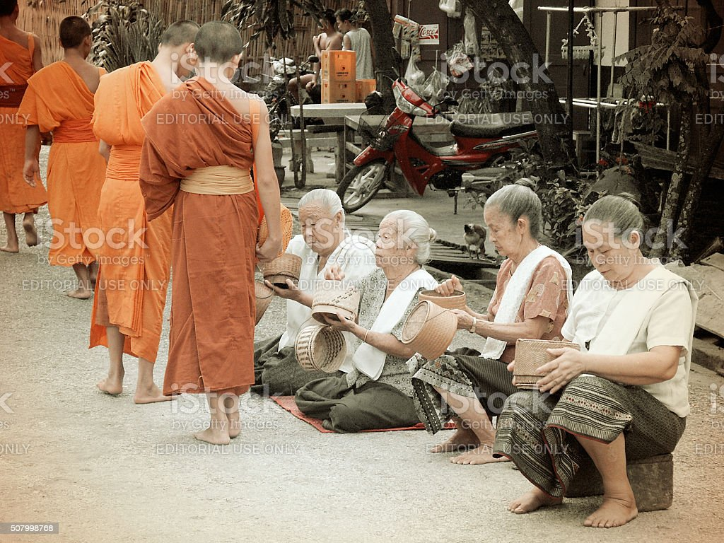 People giving alms to monks in Luang Prabang, Laos stock photo