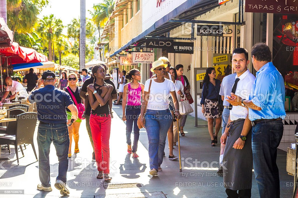 people go shopping in the afternoon sun in Lincoln Road Miami, USA - August 1, 2013: people go shopping in the afternoon sun in Lincoln Road, Miami, USA. Lincoln Road Mall is a pedestrian-only promenade and the center of whats happening in South Beach. 2015 Stock Photo