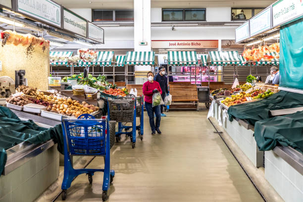 people go shopping in the central market in Portimao but wearing mouth protection to protect against Corona stock photo