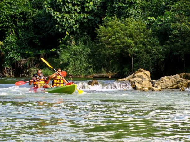 menschen nam song river hinunter, im kajak, laos - vang vieng stock-fotos und bilder