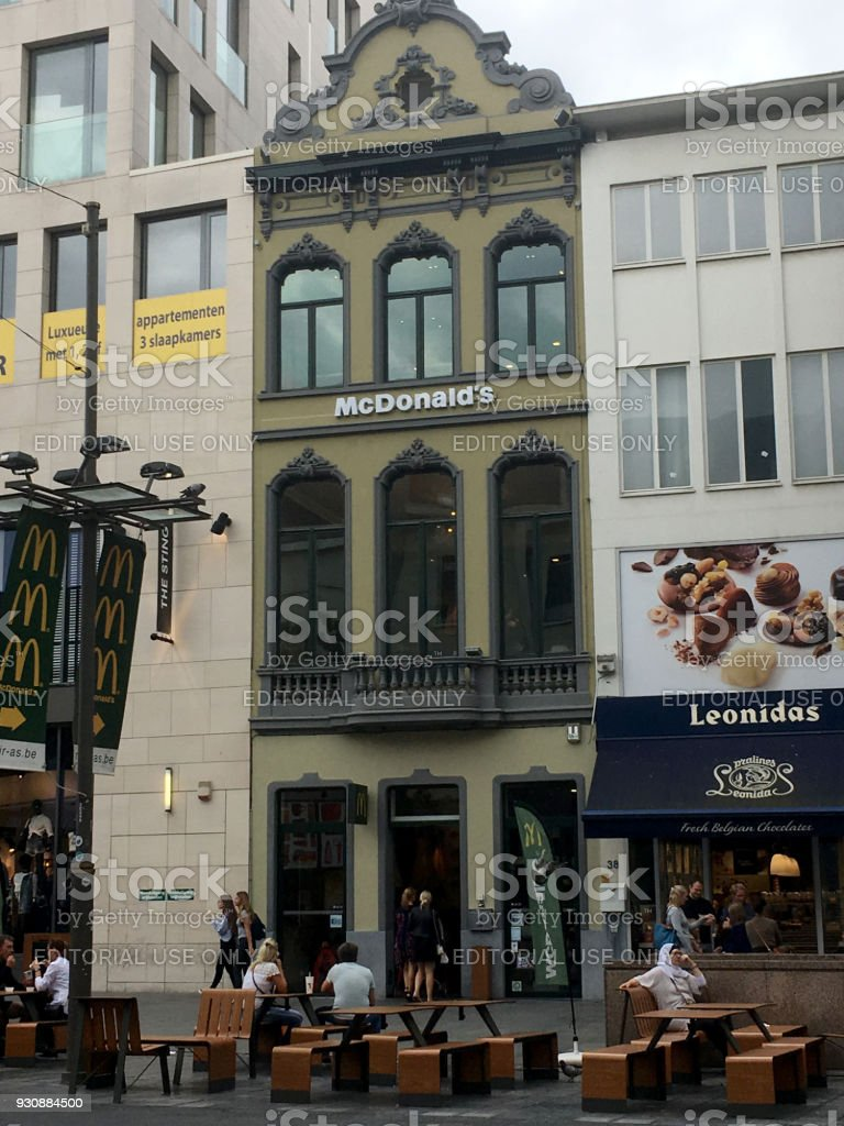 People going into a McDonald's Restaurant in Antwerp. McDonald's in an old building with traditional Dutch style roof. stock photo