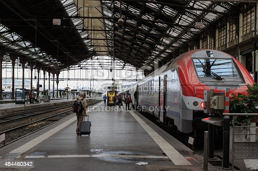 Paris, France - July 26, 2015: People going to SNCF passenger trains alongside the platforms at the Gare St Lazare. This 19th century railway station serves regional and national routes towards the north west of France. It has featured in several significant works of literature and has been the subject of various well known paintings.