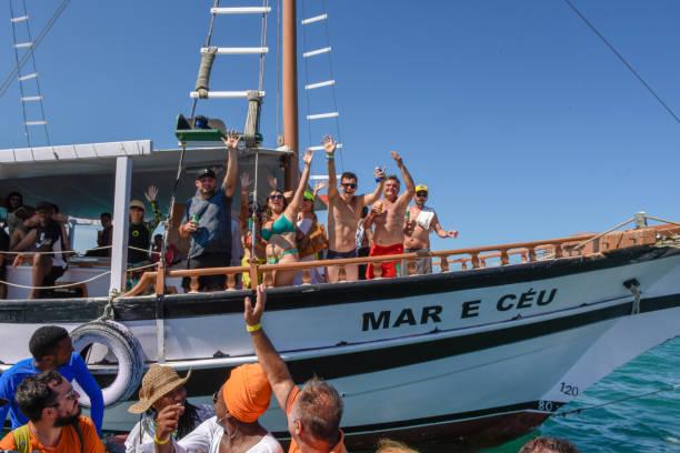 Menschen grüßen von einem Touristenboot auf der Insel Itaparica auf Brasilien – Foto