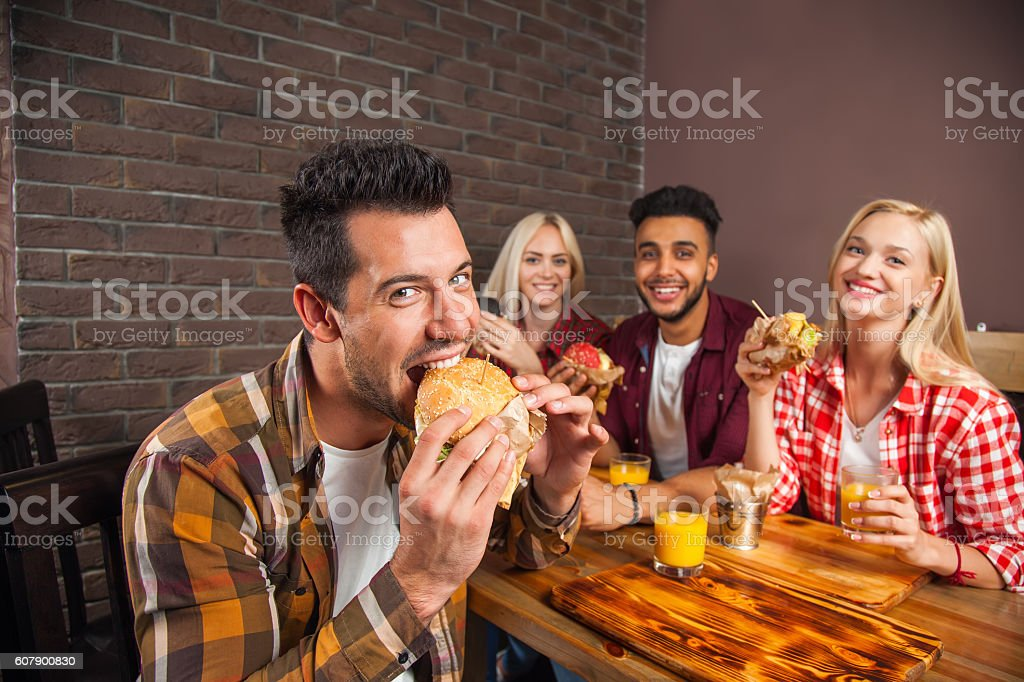 People Group Eating Fast Food Burgers Sitting At Wooden Table – Foto